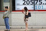 People stand by an electronic stock board of a securities firm in Tokyo, Wednesday, Aug. 21, 2019. Asia stock markets followed Wall Street lower Wednesday as investors looked ahead to a speech by the Federal Reserve chairman for signs of possible plans for more U.S. interest rate cuts. (AP Photo/Koji Sasahara)