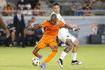 Houston Dynamo midfielder Fafa Picault (10) is pulled back as he moves the ball by Austin FC midfielder Sebastian Driussi (25) during the first half of an MLS soccer match Saturday, Sept. 11, 2021, in Houston. (AP Photo/Michael Wyke)