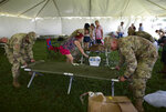 Members of the US army reserve assemble a cot as they set up a tent city to house hundreds of people displaced by earthquakes in Guanica, Puerto Rico, Tuesday, Jan. 14, 2020. More than 1,280 earthquakes have hit Puerto Rico's southern region since Dec. 28, more than two dozen of them magnitude 4.5 or greater, according to the U.S. Geological Survey. (AP Photo/Carlos Giusti)