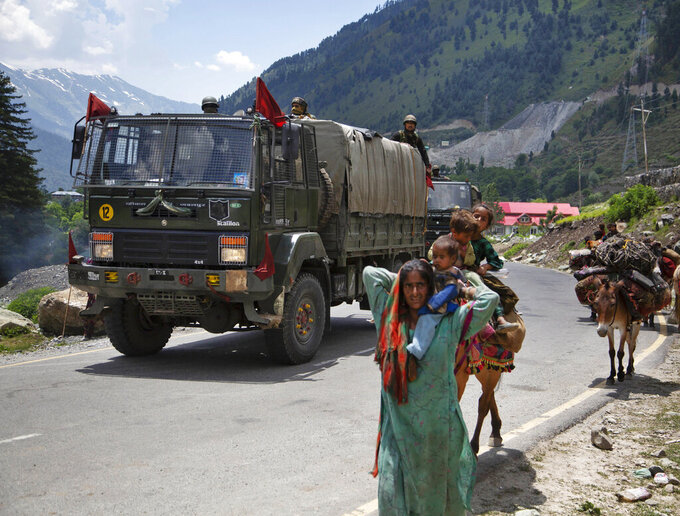 Kashmiri Bakarwal nomads walk as an Indian army convoy moves on the Srinagar- Ladakh highway at Gagangeer, north-east of Srinagar, India, Wednesday, June 17, 2020. Indian security forces said neither side fired any shots in the clash in the Ladakh region late Monday that was the first deadly confrontation on the disputed border between India and China since 1975. China said Wednesday that it is seeking a peaceful resolution to its Himalayan border dispute with India following the death of 20 Indian soldiers in the most violent confrontation in decades. (AP Photo/Mukhtar Khan)