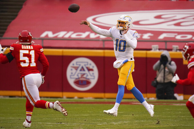 Los Angeles Chargers quarterback Justin Herbert throws a pass over Kansas City Chiefs defensive end Mike Danna (51) during the first half of an NFL football game, Sunday, Jan. 3, 2021, in Kansas City. (AP Photo/Jeff Roberson)