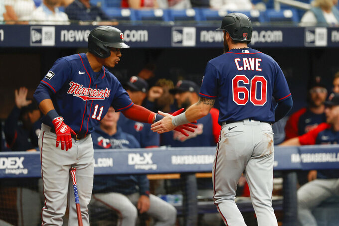 Minnesota Twins' Jake Cave (60) celebrates with teammate Jorge Polanco after scoring against the Tampa Bay Rays during the second inning of a baseball game on Sunday, Sept. 5, 2021, in St. Petersburg, Fla. (AP Photo/Scott Audette)