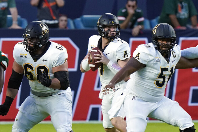 Appalachian State quarterback Chase Brice, center, looks for an open teammate as he is guarded by offensive lineman Isaiah Helms (68) and offensive lineman Baer Hunter (51) during the first half of an NCAA college football game against Miami, Saturday, Sept. 11, 2021, in Miami Gardens, Fla. (AP Photo/Wilfredo Lee)