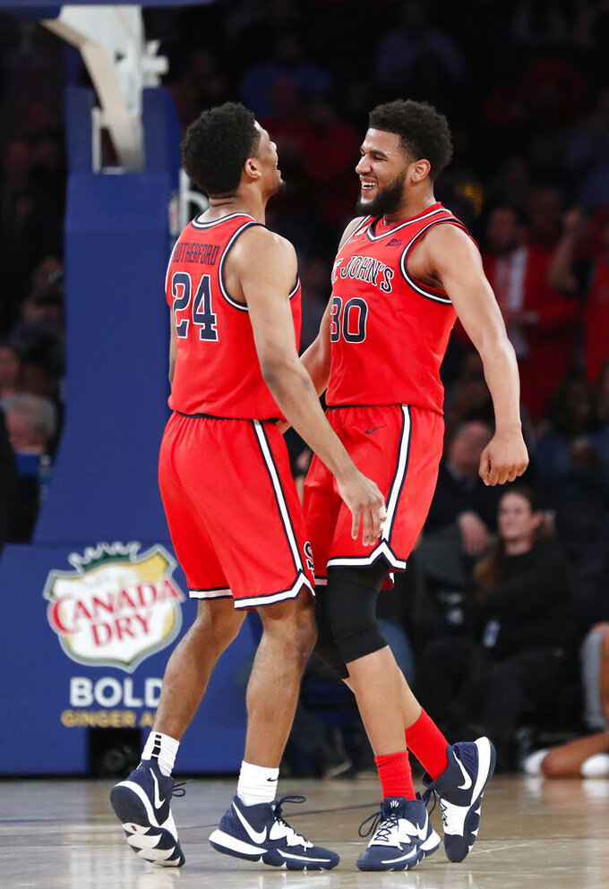 St. John's guard LJ Figueroa (30) celebrates with guard Nick Rutherford (24) during the second half of the team's NCAA college basketball game  against Georgetown in the first round of the Big East men's tournament Wednesday, March 11, 2020, in New York. (AP Photo/Kathy Willens)