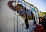 Volunteers paint an image of an elephant named