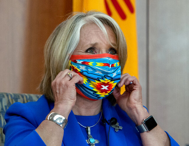 New Mexico Gov. Michelle Lujan Grisham removes her face mask at the start of an update on the COVID-19 outbreak in New Mexico and the State's effort to limit the impact of the disease on residents, during a news conference at the State Capitol in Santa Fe, N.M., Wednesday May 27, 2020. (Eddie Moore/The Albuquerque Journal via AP)
