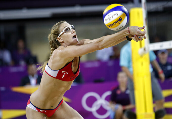 """FILE - In this Wednesday, Aug. 8, 2012, file photo, Kerri Walsh Jennings sets the ball during the women's Gold medal beach volleyball match between two United States teams at the 2012 Summer Olympics in London. For two decades, no one loomed larger in beach volleyball than five-time Olympian Kerri Walsh Jennings. But when the Summer Games begin in Tokyo this month, she won't be there. The 42-year-old Californian known as """"Six Feet of Sunshine"""" was foiled in her attempt to make a sixth Summer Games. (AP Photo/Dave Martin, File)"""