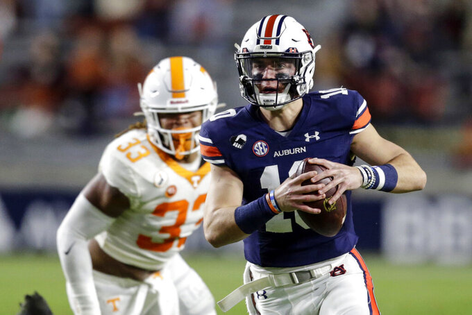 FILE - In this Saturday, Nov. 21, 2020, file photo, Auburn quarterback Bo Nix (10) scrambles during the first half of an NCAA college football game against Tennessee in Auburn, Ala. Alabama quarterback Mac Jones and Auburn's Bo Nix have taken different paths to their starting jobs. Now, they'll lead their teams into the Iron Bowl for the second straight year.  (AP Photo/Butch Dill, File)