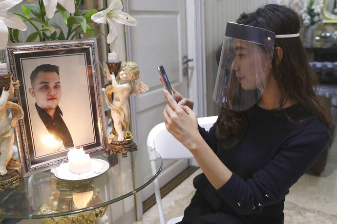 Tri Novia Septiani takes a photo of a portrait of her fiance Dr. Michael Robert Marampe during an online memorial service to mark the 40th day since Marampe passed away due to COVID-19 in Jakarta, Indonesia, on June 5, 2020. Marampe knew what he wanted to be since he was a kid: a doctor and a pianist. He became both, and his passion for music even led him to Septiani - a woman he never got to marry because he got the coronavirus. Marampe became one of dozens of doctors the coronavirus has claimed so far in Indonesia. (AP Photo/Tatan Syuflana)