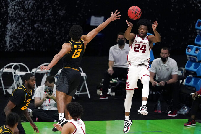 Oklahoma guard Elijah Harkless (24) passes over Missouri guard Mark Smith (13) during the second half of a first-round game in the NCAA men's college basketball tournament at Lucas Oil Stadium, Saturday, March 20, 2021, in Indianapolis. (AP Photo/Darron Cummings)