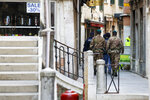 Police officers and soldiers patrol streets to enforce the lockdown, in Venice, Monday, April 6, 2020. The government is demanding Italians stay home and not take the leveling off of new coronavirus infections as a sign the emergency is over, following evidence that more and more Italians are relaxing restrictions the west's first and most extreme nationwide lockdown and production shutdown. The new coronavirus causes mild or moderate symptoms for most people, but for some, especially older adults and people with existing health problems, it can cause more severe illness or death. (AP Photo/Andrew Medichini)