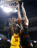 Southern California's Victor Uyaelunmo, center, goes up to basket under pressured by KZ Okpala, left, and Josh Sharma during the first half of an NCAA college basketball game Sunday, Jan. 6, 2019, in Los Angeles. (AP Photo/Ringo H.W. Chiu)