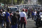 Service trucks line up to remove trash left behind by anti-austerity protesters, in Quito, Ecuador, Monday, Oct. 14, 2019. Thousands of indigenous demonstrators, student volunteers and local residents launched a massive cleanup Monday morning of a Quito park where anti-austerity protesters fought police for days, leaving piles of burning tires, trees and construction material. (AP Photo/Fernando Vergara)