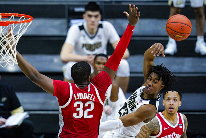 Purdue guard Jaden Ivey (23) makes a pass away from Ohio State forward E.J. Liddell (32) in the second half of an NCAA college basketball game at the Big Ten Conference tournament in Indianapolis, Friday, March 12, 2021. Ohio State defeated Purdue 87-78 in overtime. (AP Photo/Michael Conroy)