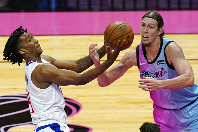 LA Clippers guard Jay Scrubb (4) and Miami Heat forward Kelly Olynyk (9) go after a rebound during the first half of an NBA basketball game, Thursday, Jan. 28, 2021, in Miami. (AP Photo/Marta Lavandier)