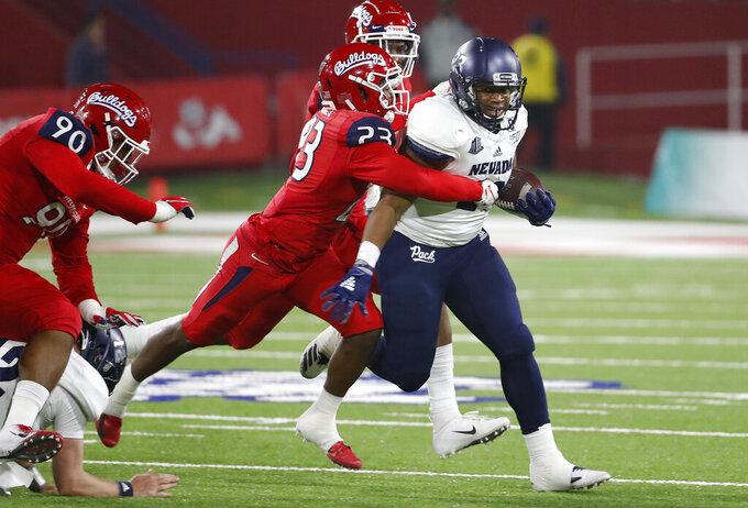 Nevada running back Kelton Moore tries to shake loose from Fresno State defensive back Juju Hughes during the first half of an NCAA college football game in Fresno, Calif., Saturday, Nov. 23, 2019. (AP Photo/Gary Kazanjian)