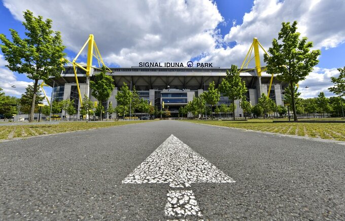 A directional arrow on a street points to the Signal Iduna Park, Germany's biggest stadium of Borussia Dortmund in Dortmund, Germany, Thursday, May 14, 2020. Bundesliga will now restart on May 16, 2020 when Borussia Dortmund will play the derby against FC Schalke 04 at home without spectators due to the coronavirus outbreak. (AP Photo/Martin Meissner)