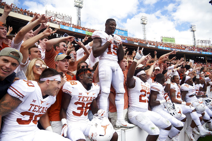 Texas players celebrates after defeating Oklahoma 48-45 in an NCAA college football game at the Cotton Bowl, Saturday, Oct. 6, 2018, in Dallas. (AP Photo/Cooper Neill)