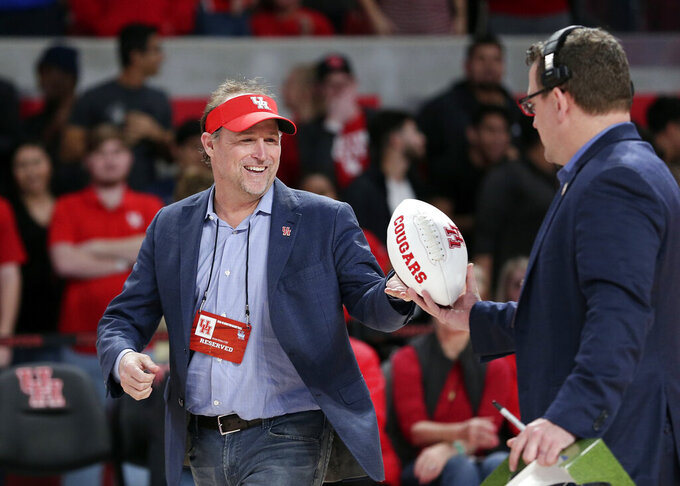 FILE - In this Jan. 2, 2019, file photo, Dana Holgorsen, the newly named football coach for the Houston college football team, gets autographed footballs to toss to the crowd as he is recognized during halftime of an NCAA college basketball game between Tulsa and Houston, in Houston. (AP Photo/Michael Wyke, File)
