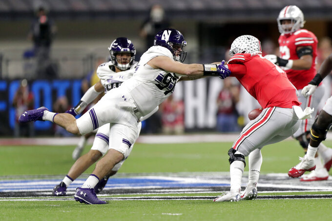 Northwestern defensive lineman Joe Gaziano, left, tackles Ohio State quarterback Dwayne Haskins during the second half of the Big Ten championship NCAA college football game, Saturday, Dec. 1, 2018, in Indianapolis. (AP Photo/Michael Conroy)