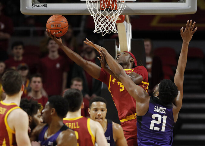 Iowa State forward Solomon Young, center, finds a shot around TCU center Kevin Samuel during the second half of an NCAA college basketball game, Tuesday, Feb. 25, 2020, in Ames, Iowa. Iowa State won 65-59. (AP Photo/Matthew Putney)