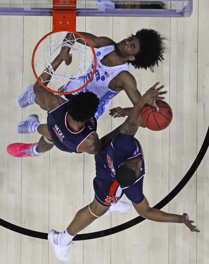 North Carolina's Coby White, top, loses control of the ball as Auburn's Chuma Okeke and Horace Spencer, bottom, defend during the first half of a men's NCAA tournament college basketball Midwest Regional semifinal game Friday, March 29, 2019, in Kansas City, Mo. (AP Photo/Charlie Riedel)