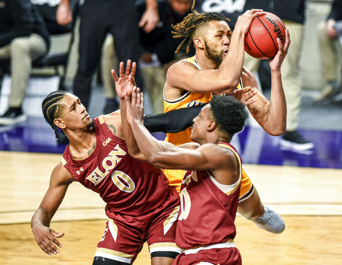 Drexel forward Tim Perry Jr. (13) is fouled by Elon guard Hunter McIntosh (0) during the first half of an NCAA college basketball game for the Colonial Athletic Association men's tournament championship in Harrisonburg, Va., Tuesday, March 9, 2021. (AP Photo/Daniel Lin)