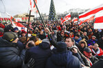 Protesters argue with pro-government people dressed in black during a rally in downtown Minsk, Belarus, Saturday, Dec. 7, 2019. Several hundreds demonstrators gathered to protest against closer integration with Russia. (AP Photo/Sergei Grits)