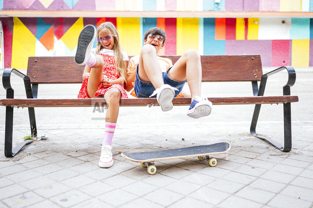 Playful friends sitting on bench