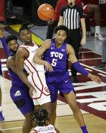 Oklahoma's Victor Iwuakor, center, and TCU's Chuck O'Bannon Jr. (5) watch O'Bannon's pass during the second half of an NCAA college basketball game in Norman, Okla., Tuesday, Jan. 12, 2021. (AP Photo/Garett Fisbeck)