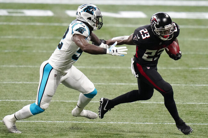 Atlanta Falcons running back Brian Hill (23) runs against Carolina Panthers middle linebacker Tahir Whitehead (52) during the first half of an NFL football game, Sunday, Oct. 11, 2020, in Atlanta. (AP Photo/Brynn Anderson)