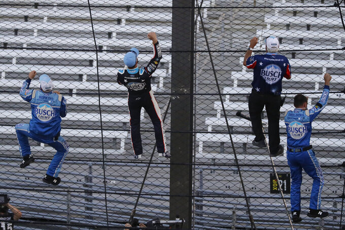 Kevin Harvick, second from left, and some members of the team's crew climb the fence after Harvick won the NASCAR Cup Series auto race at Indianapolis Motor Speedway in Indianapolis, Sunday, July 5, 2020. (AP Photo/Darron Cummings)