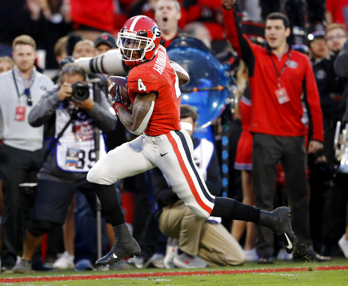 Georgia wide receiver Mecole Hardman (4) looks over his shoulder as he runs for a touchdown on a pass from quarterback Justin Fields during the first half of an NCAA college football game against Massachusetts Saturday, Nov. 17, 2018, in Athens, Ga. (AP Photo/John Bazemore)