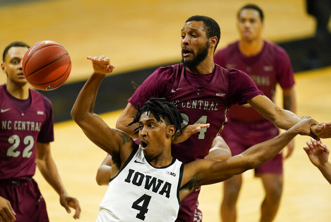 Iowa guard Ahron Ulis (4) fights for a rebound with North Carolina Central guard Nicolas Fennell (24) during the second half of an NCAA college basketball game, Wednesday, Nov. 25, 2020, in Iowa City, Iowa. Iowa won 97-67. (AP Photo/Charlie Neibergall)