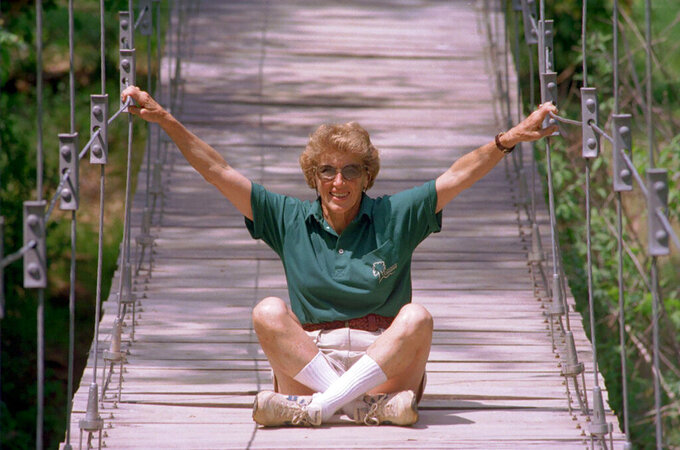 Anne Springs Close sits over Steele Creek on a suspended bridge at her Anne Springs Close Greenway just north of Fort Mill, S.C., off of U.S. Route 21 bypass on April 20, 1995. Close who used her family's textile fortune to give back to the community through education and land preservation has died at age 95. Close's family says she died Friday, Aug. 20, 2021, from injuries suffered when a tree branch fell on her at her property in Fort Mill, S.C., a few days earlier. (Layne Bailey/The Charlotte Observer via AP)