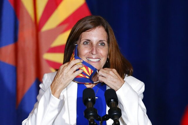 FILE - In this Tuesday, Aug. 11, 2020 file photo, Sen. Martha McSally, R-Ariz., smiles as she removes her face covering to speak prior to Vice President Mike Pence arriving to speak at the