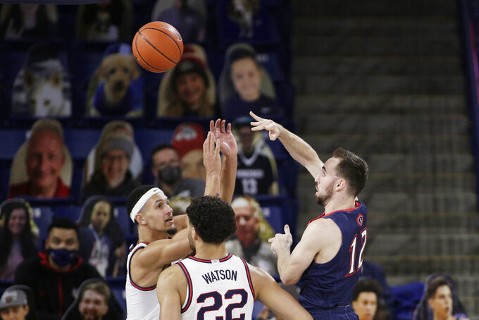 Saint Mary's guard Tommy Kuhse, right, passes the ball past Gonzaga guard Jalen Suggs, left, and forward Anton Watson during the first half of an NCAA college basketball game in Spokane, Wash., Thursday, Feb. 18, 2021. (AP Photo/Young Kwak)