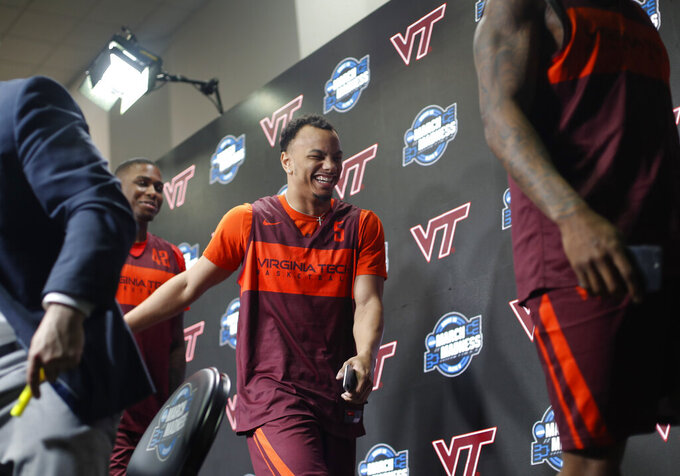Virginia Tech guard Justin Robinson, center, smiles as he walks off stage with teammates Ty Outlaw, left, and Ahmed Hill, right, at the conclusion of a news conference at the NCAA men's college basketball tournament in Washington, Thursday, March 28, 2019. Virginia Tech plays Duke in an East Regional semifinal game on Friday. (AP Photo/Pablo Martinez Monsivais)