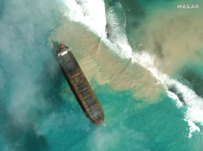 """In this satellite image provided by 2020 Maxar Technologies on Friday, Aug. 7, 2020, an aerial view of the MV Wakashio, a bulk carrier ship that recently ran aground off the southeast coast of Mauritius. The prime minister of Mauritius says the government is appealing to France for help with a brewing environmental disaster after a ship that ran aground almost two weeks ago off the Indian Ocean island nation began leaking oil. Prime Minister Pravind Jugnauth said Friday that the leak """"represents a danger for Mauritius"""