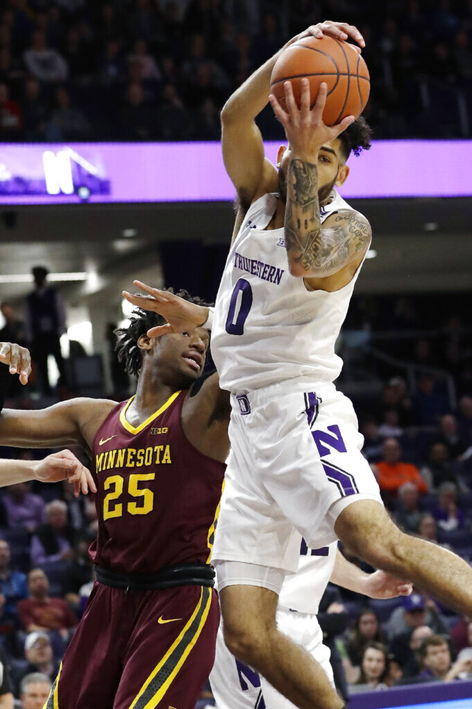 Northwestern guard Boo Buie, right, rebounds a ball against Minnesota center Daniel Oturu during the first half of an NCAA college basketball game in Evanston, Ill., Sunday, Feb. 23, 2020. (AP Photo/Nam Y. Huh)