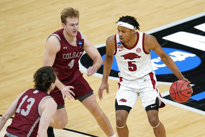 Arkansas' Moses Moody (5) is defended by Colgate's Jack Ferguson (13) and Ryan Moffatt (4) during the second half of a first round game at Bankers Life Fieldhouse in the NCAA men's college basketball tournament, Friday, March 19, 2021, in Indianapolis. (AP Photo/Darron Cummings)