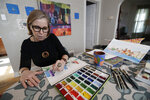 In this Jan. 8, 2020, photo Marian Nixon paints at her home in Chicago. Nixon finds its easier for her prints, clothes and sketch books to be seen on Amazon rather than on her own website. But selling online presents challenges that can be hard, even impossible to overcome. She gets good reviews for her designs, but she's had bad reviews when something has gone wrong with shipping, which is out of her control. (AP Photo/Nam Y. Huh)
