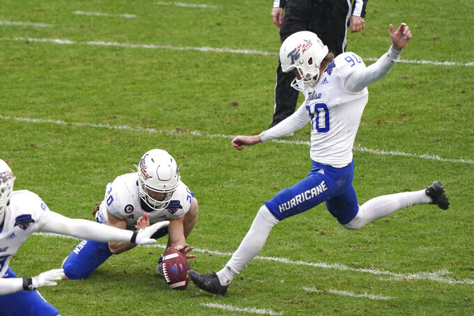 Tulsa wide receiver Cannon Montgomery (20) holds the ball as place kicker Zack Long (90) kicks a field goal against Mississippi State during the first half of the Armed Forces Bowl NCAA college football game Thursday, Dec. 31, 2020, in Fort Worth, Texas. (AP Photo/Jim Cowsert)