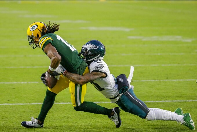Green Bay Packers' Davante Adams catches a pass with Philadelphia Eagles' Jalen Mills defending during the first half of an NFL football game Sunday, Dec. 6, 2020, in Green Bay, Wis. (AP Photo/Mike Roemer)