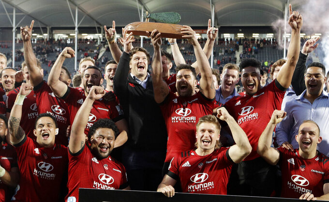 Crusaders Codie Taylor and injured teammate Scott Barrett hold the Super Rugby Aotearoa trophy aloft after defeating the Highlanders in Christchurch, New Zealand, Sunday, Aug. 9, 2020. (AP Photo/Mark Baker)