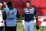 Bryson DeChambeau prepares to fist-bump Troy Merritt's caddie after winning the Rocket Mortgage Classic golf tournament Sunday, July 5, 2020, at Detroit Golf Club in Detroit. (AP Photo/Carlos Osorio)