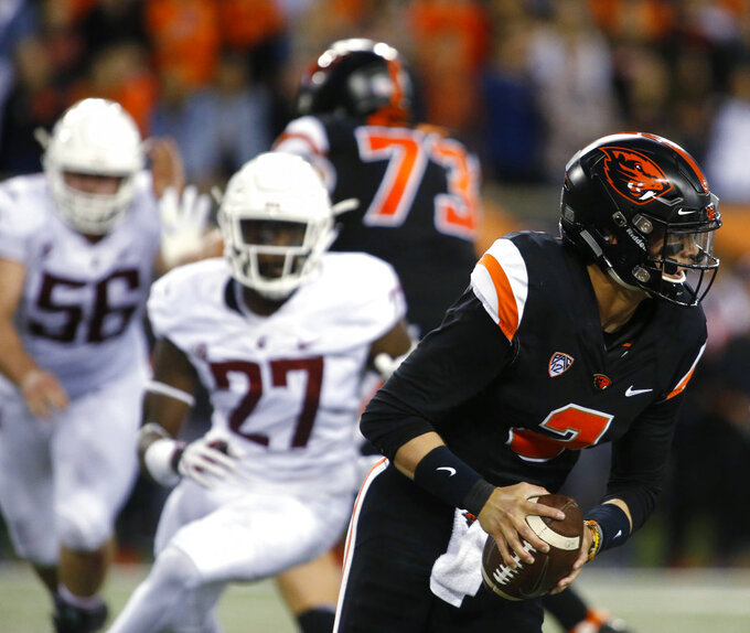 Oregon State quarterback Conor Blunt (2) scrabbles away from Washington State's Taylor Comfort (56) and Willie Taylor III (27) during the first half of an NCAA college football in Corvallis, Ore., Saturday, Oct. 6, 2018. (AP Photo/Timothy J. Gonzalez)