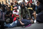Protesters reenact the scene where George Floyd was restrained by police while marching in a solidarity rally calling for justice over the death of George Floyd Tuesday, June 2, 2020, in New York. Floyd died after being restrained by Minneapolis police officers on May 25. (AP Photo/Wong Maye-E)