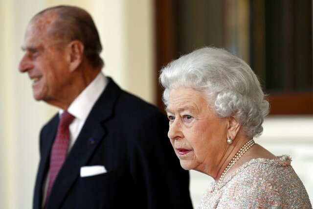 FILE - In this Thursday, Nov. 3, 2016 file photo, Britain's Prince Philip and Queen Elizabeth II bid farewell to Colombia's President Juan Manuel Santos, and his wife Maria Clemencia de Santos, following their state visit, at Buckingham Palace in London. Queen Elizabeth II and her husband have received their COVID-19 vaccinations. Buckingham Palace officials said in a statement that the 94-year-old monarch and 99-year-old Prince Philip received their jabs on Saturday, Jan. 9, 2021, joining some 1.5 million people in Britain who have been given the first dose of a vaccine against the coronavirus. (Stefan Wermuth/Pool Photo via AP, File)