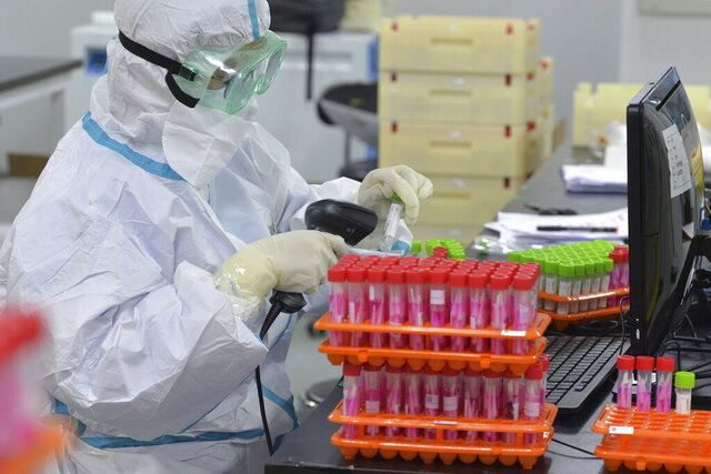 A medical worker scans the nucleic acid samples collected from a mass testing at a lab in north China's Tianjin Municipality on Monday, Nov. 23, 2020. China has reported new coronavirus cases in the cities of Shanghai and Tianjin as it seeks to prevent small outbreaks from becoming larger ones. (Chinatopix via AP)